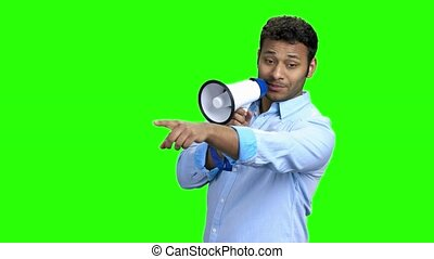 Cheerful young man with megaphone on green screen.