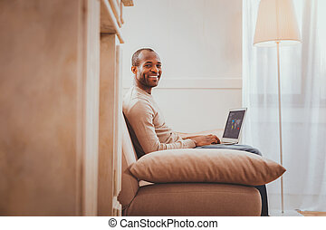 Cheerful young man working from home