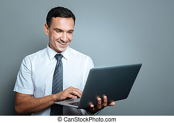 Cheerful young manager working on a laptop