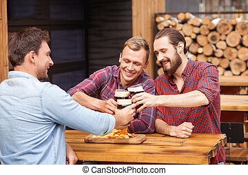Cheerful young men are resting in beerhouse