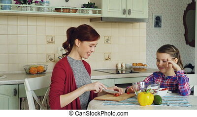 Cheerful young mother cutting tomatoes while cooking and talking to her smiling daughter feeding mom in the kitchen at home. Family, cook, and people concept