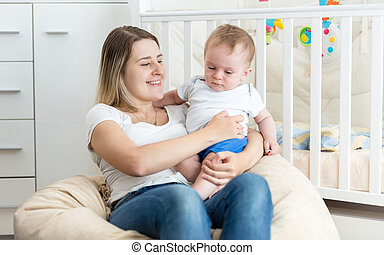 Cheerful young mother reading book to her baby boy at living room