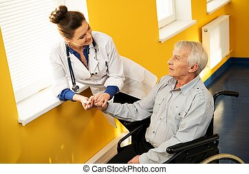 Cheerful young nurse woman with senior man in wheelchair