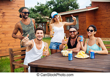 Cheerful young people drinking beer and showing thumbs up outdoors