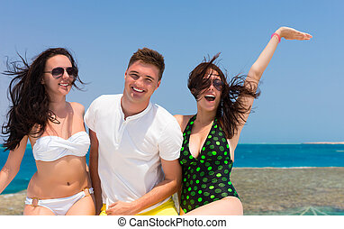 Cheerful young people laughing and standing on the yacht at...