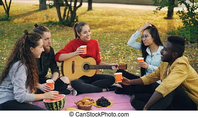 Cheerful young people multi-ethnic group are clinking...