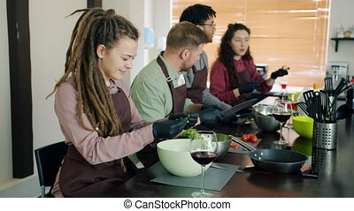 Cheerful young people multi-ethnic group cooking in cookery ...