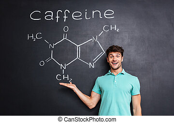 Cheerful young scientist showing chemical structure of caffeine molecule