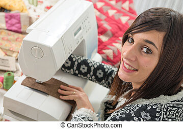 Cheerful young seamstress with her sewing machine