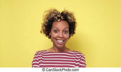 Cheerful young smiling african woman clapping hands isolated on a yellow background