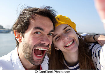 Cheerful young smiling couple taking selfie