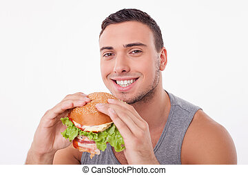 Cheerful young sportsman is enjoying unhealthy food