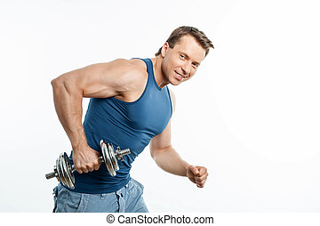 Cheerful young sportsman is exercising with dumbbell