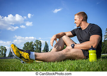 Cheerful young sportsman is resting after running