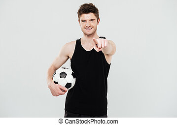 Cheerful young sportsman with foot ball pointing.