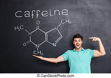 Cheerful young teacher pointing on chemical structure of caffeine molecule