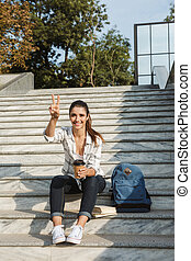 Cheerful young teenage girl sitting on a staircase