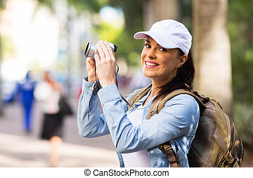 young tourist photographing in town