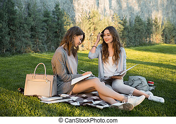 Cheerful young two women sitting outdoors in park writing notes.