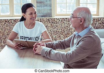 Cheerful young volunteer listening to her patient