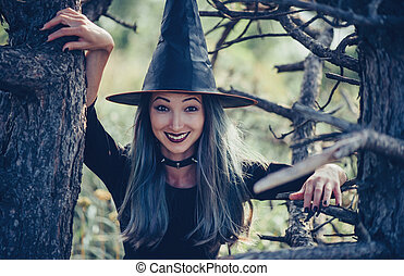 Cheerful young witch walking among old dry trees, looking at...