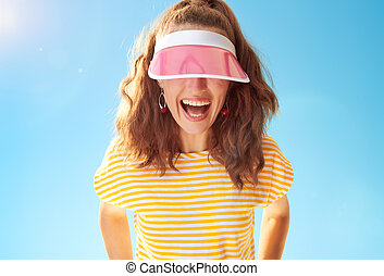 cheerful young woman against blue sky hiding behind sun ...