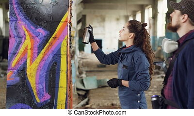 Cheerful young woman amateur graffiti artist is learning to work with spray paint from skilled bearded painter while decorating old column in empty warehouse.