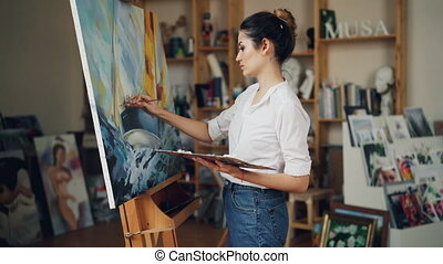 Cheerful young woman artist is painting beautiful picture...