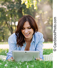 Cheerful, young woman browsing her tablet in the park