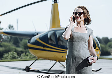 Cheerful young woman calling taxi after helicopter ride