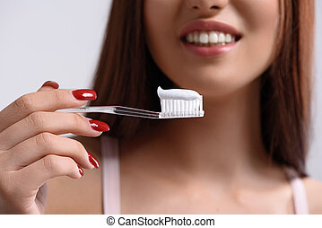 Cheerful young woman caring of her teeth