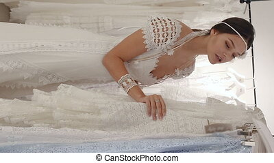young woman dressed in luxury white gown standing in wedding...