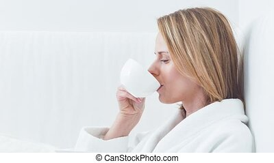 Cheerful young woman enjoying hot beverage at spa - Relaxed...