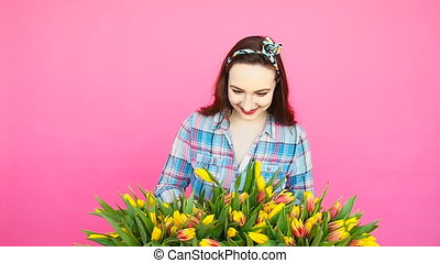 Cheerful young woman florist holding box of tulips -...