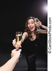 Cheerful young woman giving glass of champagne to her friend