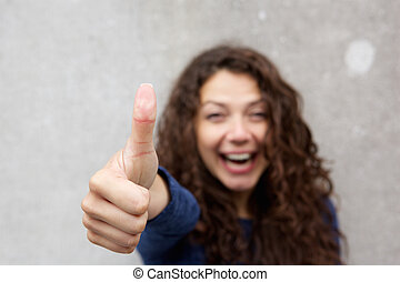 Cheerful young woman giving thumbs up