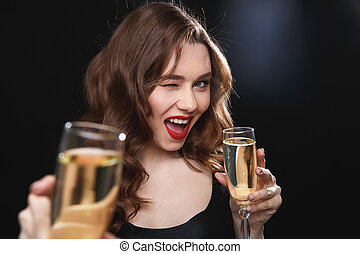 Cheerful young woman giving you glass of champagne and...