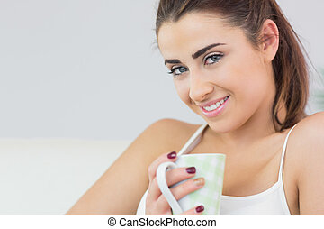 Cheerful young woman holding a cup