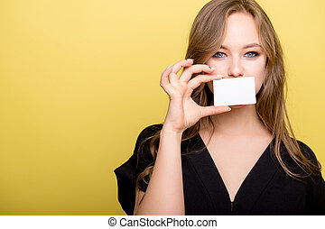 young woman holding bank card isolated on a yellow background