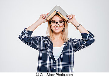 Cheerful young woman holding book
