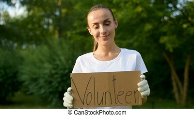 Cheerful young woman holding paper placard with volunteer inscription