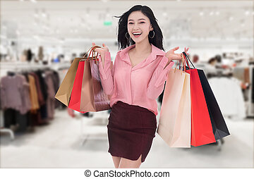 cheerful young woman holding shopping bag at mall