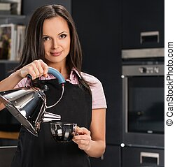 Cheerful young woman in apron on modern kitchen pouring hot drink in a cup