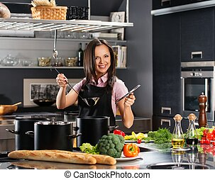 Cheerful young woman in apron on modern kitchen with ladle...