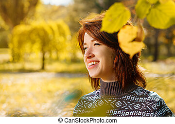 cheerful young woman in autumn Park smiling on a Sunny day