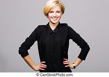 cheerful young woman in black suit on gray background