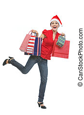 Cheerful young woman in Santa hat holding shopping bags