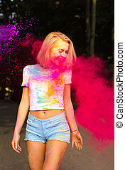 Cheerful young woman in white t shirt and jeans shorts playing with red Holi powder exploding around her