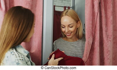 Cheerful young woman is appearing from behind curtain of fitting room while shop assistant is giving her new jumper to try on. Customer is taking garment and drawing curtain back.