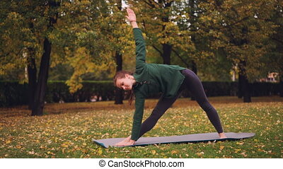 Cheerful young woman is doing yoga balancing exercises...